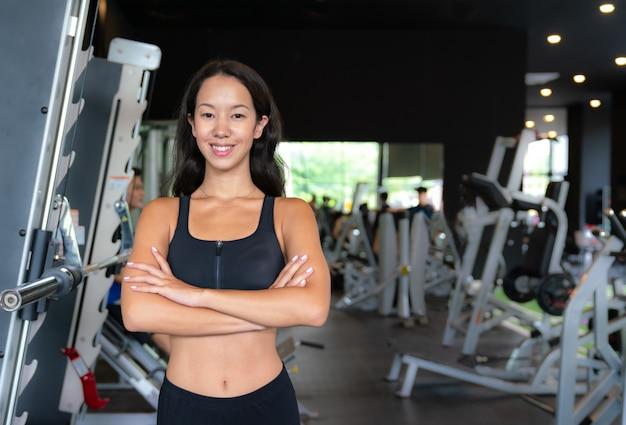 Retrato de joven asiática sonriendo y de pie en sujetador deportivo en el gimnasio
