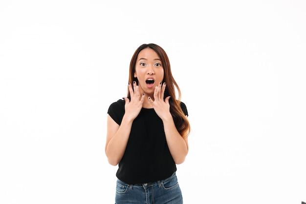 Retrato de joven asiática sorprendida en camiseta negra, mirando a la cámara