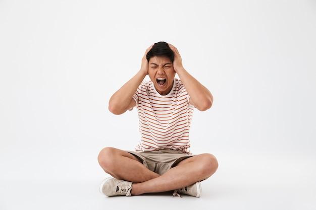 Retrato de un joven asiático enojado sentado con las piernas cruzadas