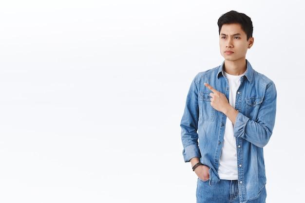 Retrato de un joven asiático escéptico, crítico y de aspecto serio, con decepción frunciendo el ceño y entrecerrando los ojos, señalando con el dedo a la izquierda juzgando algo malo, de pie en la pared blanca