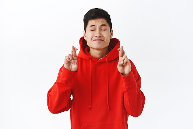 El retrato de un joven asiático esperanzado y soñador tiene deseos, cruza los dedos, buena suerte, cierra los ojos y suplica con una cara encantada y anhelante, soñando con algo malo, pared blanca.