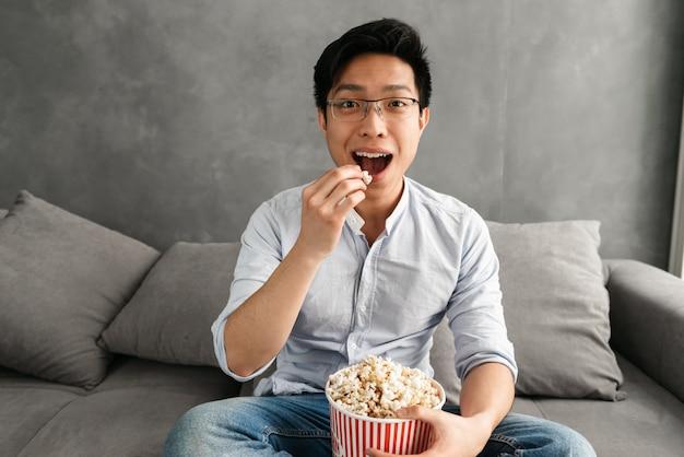 Retrato de un joven asiático feliz comiendo palomitas de maíz