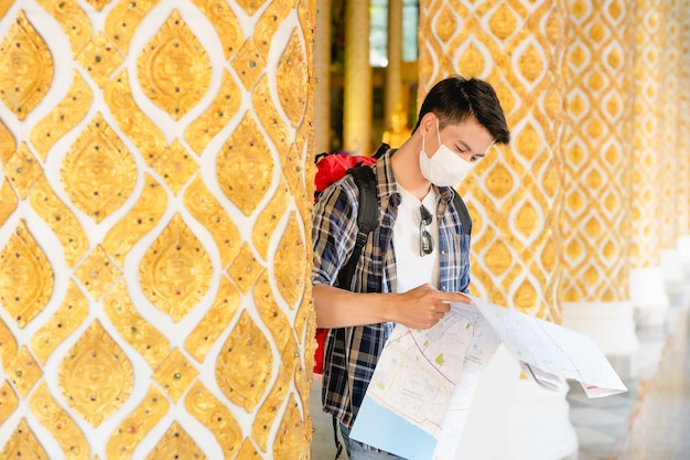 Retrato joven asiático mochilero macho en mascarilla de pie y comprobando la dirección en el mapa de papel en la mano en el hermoso templo tailandés