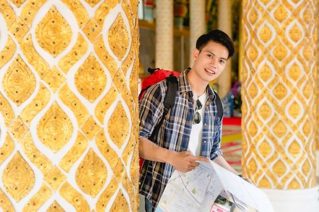 Retrato joven asiático mochilero macho de pie y comprobando la dirección en el mapa de papel en la mano en el hermoso templo tailandés y sonrisa