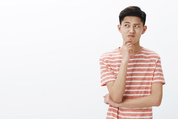 Retrato de un joven asiático con problemas tratando de pensar en un plan o una idea, de pie en una pose pensativa con la mano en la barbilla, mirando cuestionado y vacilante en la esquina superior izquierda