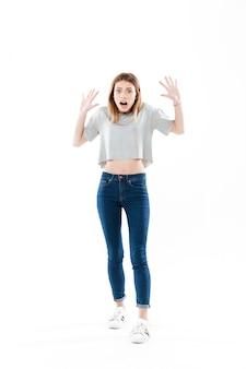 Retrato de una joven asustada de pie y gritando