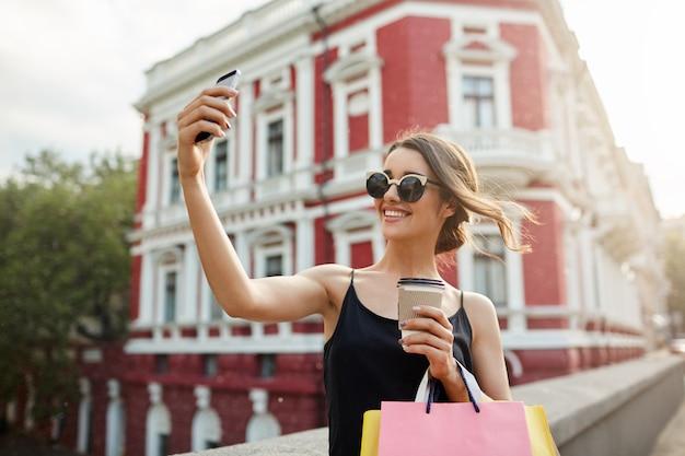 Retrato de joven atractiva chica caucásica femenina con cabello oscuro en gafas color canela y vestido negro sonriendo brillantemente tomando fotos frente a hermoso edificio rojo, bebiendo café, sosteniendo bolsas.