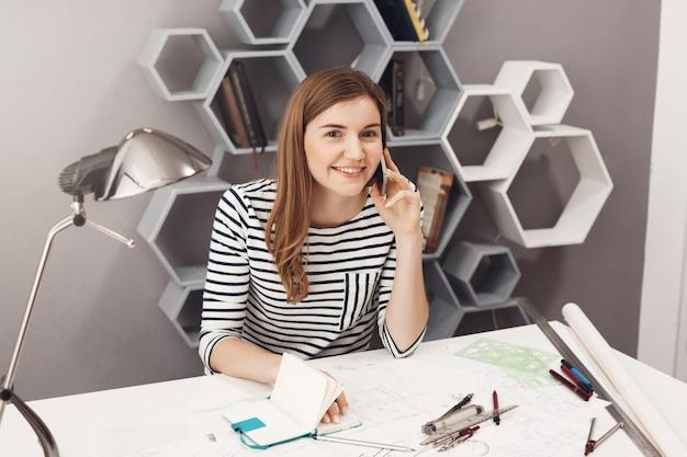 Retrato de joven y atractiva chica de diseñador de pelo oscuro alegre sentado en el lugar de coworking, hablando por teléfono, escribiendo notas con suave sonrisa y expresión feliz.