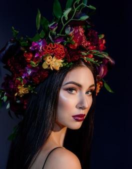 Retrato de joven atractiva con maquillaje brillante vestida con una gran corona floral colorida