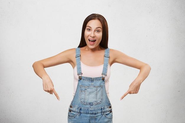 Retrato de joven y atractiva mujer morena con camiseta blanca y overol de mezclilla, apuntando con los dedos hacia abajo, con expresión feliz mientras anuncia algo. mujer mostrando algo