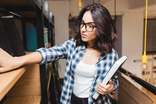 Retrato joven atractiva mujer morena de gafas negras en la biblioteca en busca de libros. estudiante inteligente, tiempo de estudio, buen trabajo, académico.