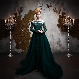 Retrato de joven atractiva mujer rubia en un hermoso vestido verde. fondo texturizado, interior. peinado de lujo