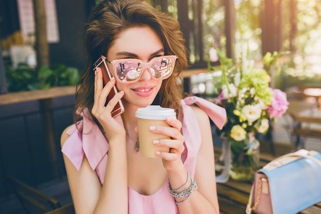 Retrato de joven atractiva mujer sentada en la cafetería, traje de moda de verano, vestido de algodón rosa, gafas de sol, sonriente, tomando café, accesorios elegantes, ropa de moda, hablando por teléfono