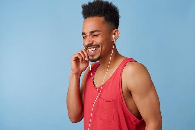Retrato de joven atractivo afroamericano feliz con una camiseta roja escucha música favorita y disfruta del ambiente, sostiene el auricular con la mano derecha, cierra los ojos, se pone de pie.