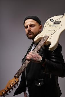 Retrato de un joven atractivo con una chaqueta de cuero y tatuajes con una guitarra eléctrica en el hombro fondo oscuro