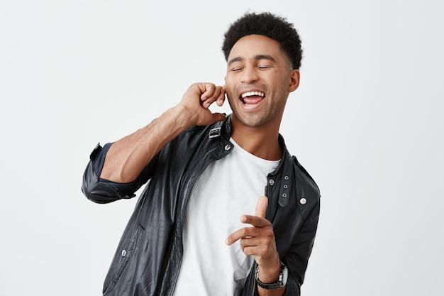 Retrato de joven atractivo estudiante americano de piel negra con cabello rizado en camiseta blanca y chaqueta de cuero cerrando los ojos, sosteniendo el dedo cerca de la oreja, cantando en voz alta en la fiesta.
