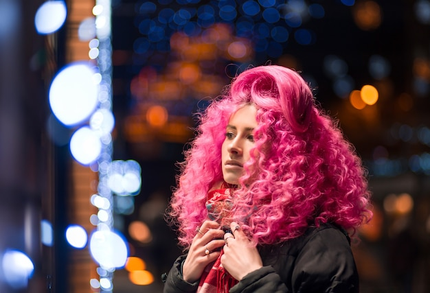 Retrato joven atractivo modelo de chica caucásica con pelo rosa brillante rizado estilo afro