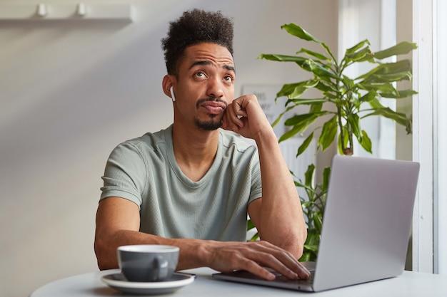 Retrato de joven y atractivo muchacho de pensamiento afroamericano, se sienta en un café, trabaja en una computadora portátil y bebe café aromático, toca la mejilla y mira hacia arriba, piensa en el próximo viaje.