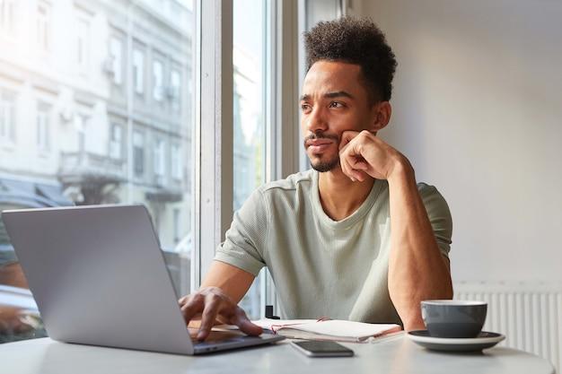 Retrato de joven atractivo muchacho de pensamiento afroamericano, se sienta en una mesa en un café, trabaja en una computadora portátil y bebe café aromático y mira pensativamente a la ventana.