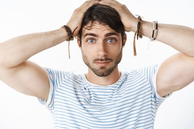 Retrato de un joven atractivo tenso con ojos azules y barba que se siente confundido y sin saber qué hacer al quedarse solo con el bebé tratando de cambiar el pañal