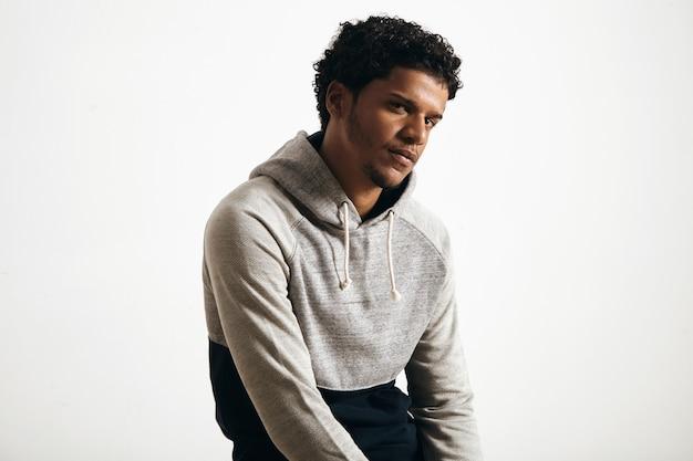 Retrato de joven atractivo vistiendo ropa normcore en blanco con capucha de asiento gris en serio