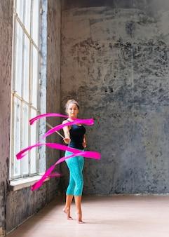 Retrato de una joven bailarina gimnasta bailando con cinta rosa