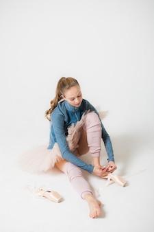 Retrato de una joven bailarina sentada en el suelo. la bailarina descansa después del entrenamiento