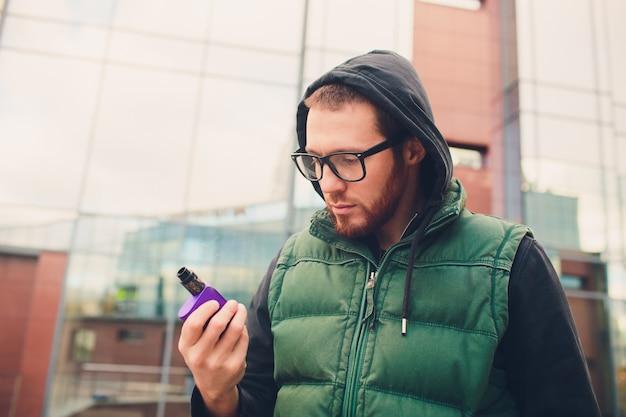 Retrato de joven con barba grande en gafas vaping un cigarrillo electrónico frente a fondo urbano.