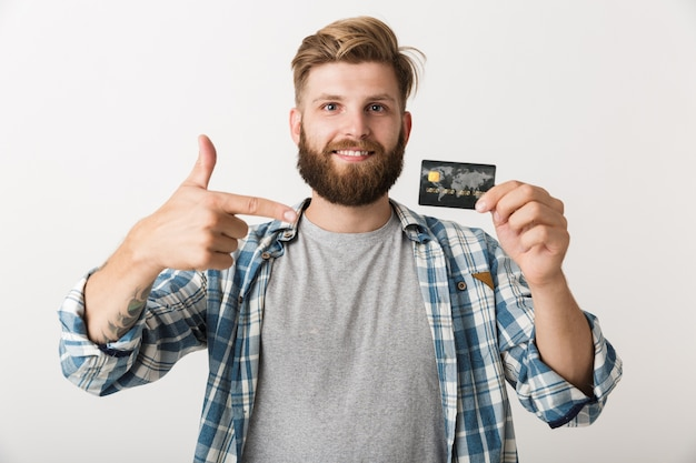 Retrato de un joven barbudo feliz mostrando tarjeta de crédito aislado sobre fondo blanco.