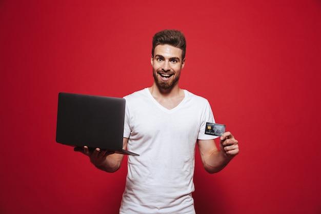 Retrato de un joven barbudo feliz sosteniendo portátil