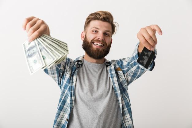 Retrato de un joven barbudo satisfecho mostrando dinero billetes y tarjetas de crédito aislado sobre fondo blanco.
