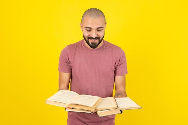 Retrato de un joven barbudo sosteniendo libros abiertos sobre pared amarilla.