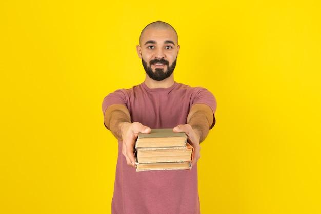 Retrato de un joven barbudo sosteniendo libros sobre pared amarilla.