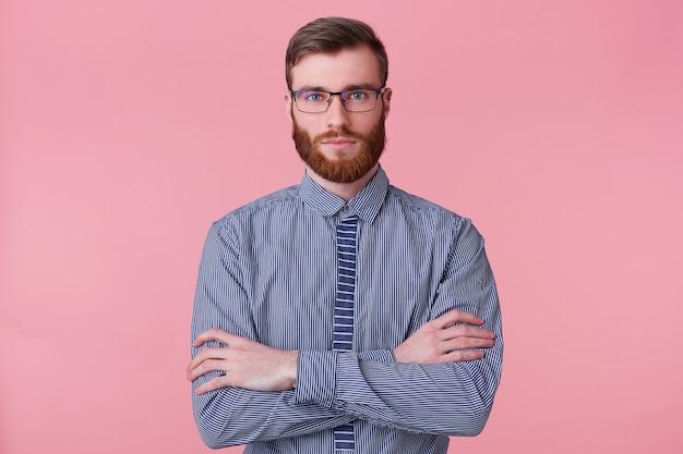 Retrato de un joven barbudo tranquilo viste una camisa a rayas, mantiene los brazos cruzados y mirando a la cámara aislada sobre un fondo rosa.