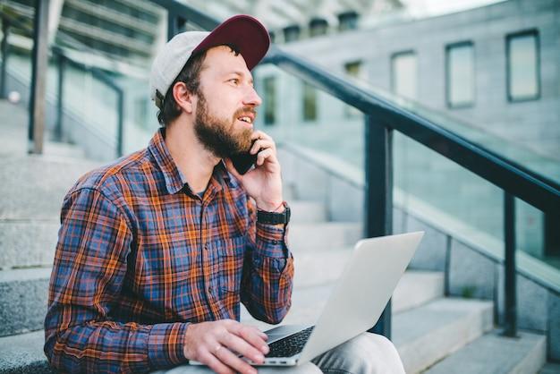 Retrato de joven barbudo vestido casualmente sentado al aire libre en los escalones del estadio, hablando por su teléfono móvil