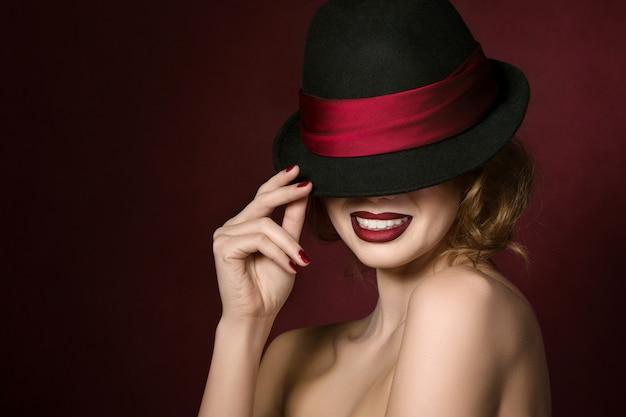 Retrato de joven bella actriz sosteniendo un sombrero negro con cinta roja