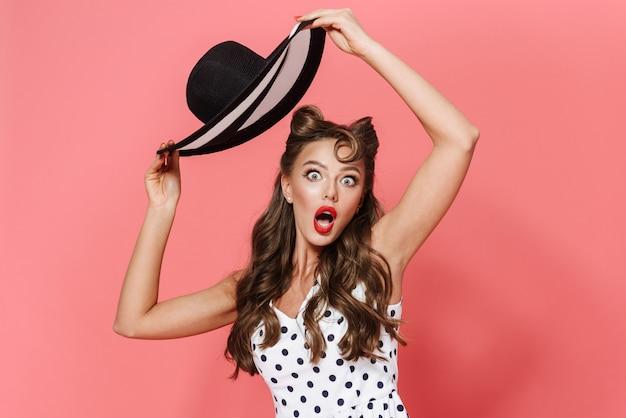 Retrato de una joven y bella chica pin-up con un vestido que se encuentran aisladas, posando, sosteniendo un sombrero de playa