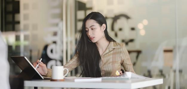 Retrato de joven y bella diseñadora asiática que trabaja en su proyecto mientras usa tableta digital