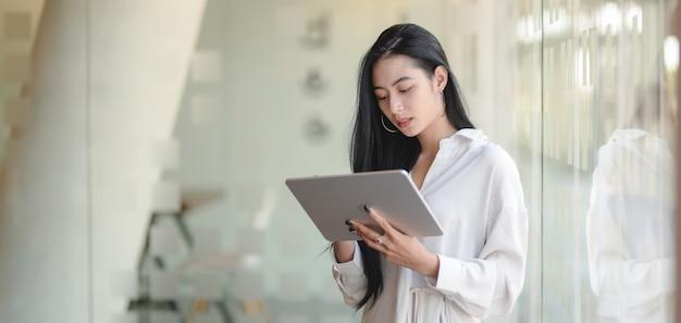 Retrato de joven bella empresaria trabajando en su proyecto mientras usa tableta digital en la oficina moderna