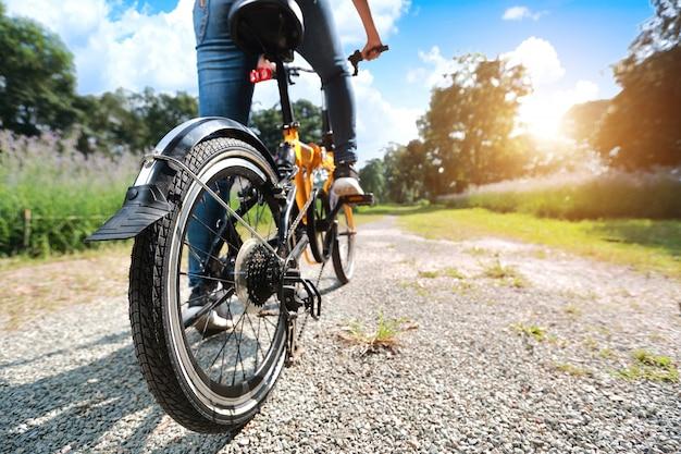 Retrato de joven bella y hipster mujer montando bicicleta y divirtiéndose entre la naturaleza