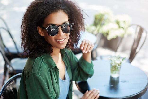 Retrato de joven bella mujer africana en sungasses sonriendo descansando relajante en el café en la terraza.