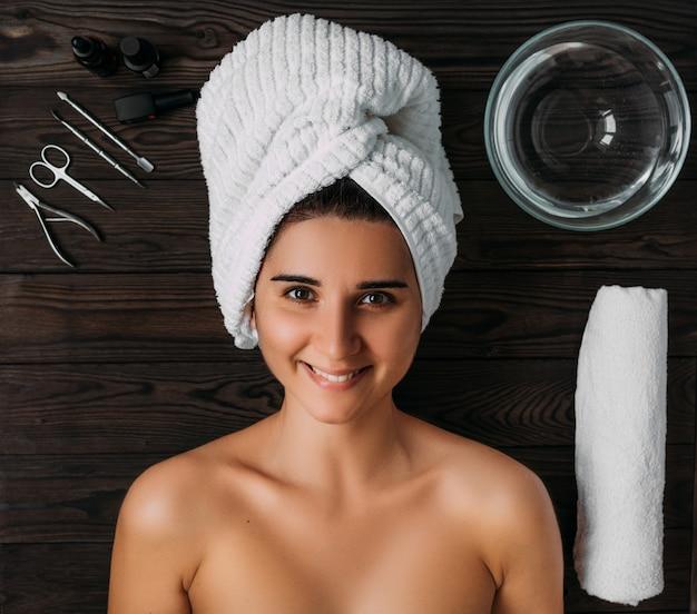 Retrato de joven bella mujer en ambiente de spa. una mujer cuida su cuerpo. cuidado del cuerpo femenino. cuidado de uñas manicura y pedicura. chica con una toalla sobre su cabeza.