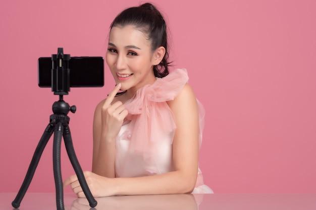 Retrato de joven y bella mujer asiática belleza profesional vlogger o blogger grabación para compartir en las redes sociales por teléfono inteligente en trípode.