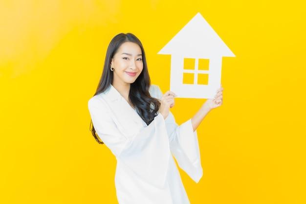 Retrato de joven y bella mujer asiática con casa de papel en la pared amarilla