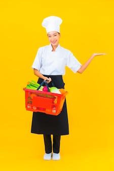 Retrato joven y bella mujer asiática chef con canasta de supermercado sobre fondo amarillo aislado