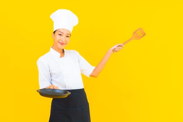 Retrato joven y bella mujer asiática chef con espátula sobre fondo amarillo aislado