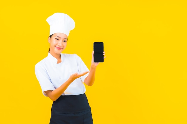 Retrato joven y bella mujer asiática chef con teléfono móvil inteligente sobre fondo amarillo aislado