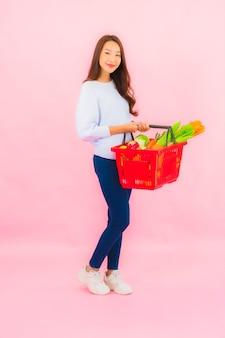 Retrato joven y bella mujer asiática con frutas y verduras y abarrotes en la canasta en la pared aislada rosa