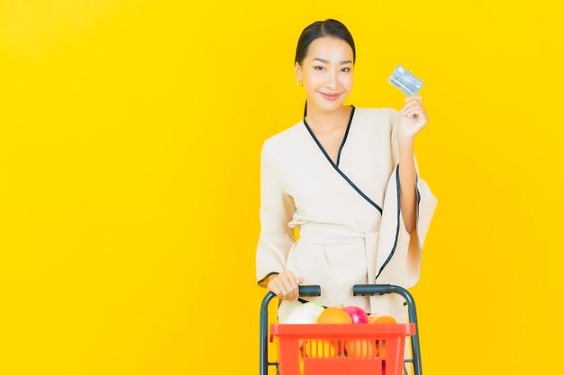 Retrato de joven y bella mujer asiática de negocios con la cesta de la compra de comestibles del supermercado en la pared amarilla