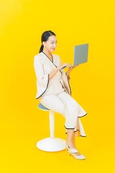 Retrato de joven y bella mujer asiática de negocios con ordenador portátil en la pared amarilla